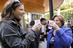 Two women clink glasses in front of a so